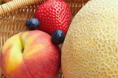 Fruit foursome. Arrangement of peach, strawberry, cantaloupe, and blueberries in a basket Royalty Free Stock Images