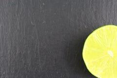 Fruit frais de chaux sur une texture de fond de nourriture de plat d'ardoise Photo stock