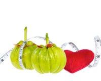 Fruit frais de gomme-gutte de Garcinia avec le coeur rouge et la bande de mesure, Photo stock