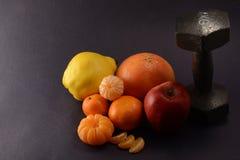 Fruit frais et haltère sur un fond foncé Concept de sport images stock