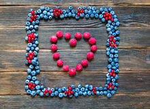Fruit frame of blueberries and red currants with heart of raspbe. Rries. Tasty summer fruits. Top view. Rustic style. Mix of different berries Stock Photos