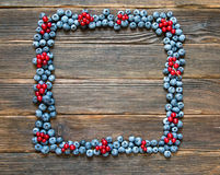 Fruit frame of blueberries and red currants. Tasty summer fruits. Top view with empty space for text. Rustic style Stock Images