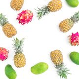 Fruit frame with pineapple, mango and dragon fruits on white background. Flat lay, top view. Food background. Stock Photos