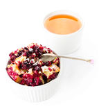 Fruit fresh crumble dessert in a white bowl with a cup of tea  o Stock Photos