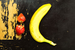 Fruit Frown. A banana and two strawberries forming a frowny icon on a scratchy wooden surface Royalty Free Stock Photo
