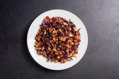 Fruit garden tea on white plate on dark backgroung Royalty Free Stock Images