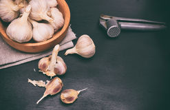 Fruit of garlic in a wooden bowl. And on a table, black wooden background Stock Image