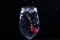 Fruit in a glass of water. Cherry fruit Water in the glass against a black background Stock Photos