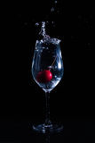 Fruit in a glass of water. Cherry fruit Water in the glass against a black background Royalty Free Stock Photo