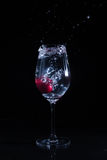 Fruit in a glass of water. Cherry fruit Water in the glass against a black background Royalty Free Stock Images