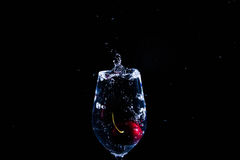 Fruit in a glass of water. Cherry fruit Water in the glass against a black background Royalty Free Stock Photos