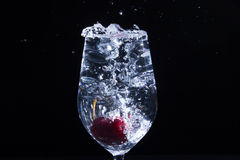 Fruit in a glass of water. Cherry fruit Water in the glass against a black background Stock Image