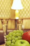 Fruit and glasses on table in interior Stock Images