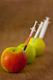 Fruit GMO. Apple pricked syringe with chemical preparation on a dark background stock images