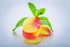Fruit gums and mint leaf. Fruit gums half yellow and half red, strawberry, and lemon with sugar on top and mint leaf Stock Photo