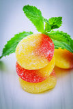Fruit gums and mint leaf. Fruit gums half yellow and half red, strawberry, and lemon with sugar on top and mint leaf Stock Photography