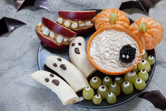 Fruit Halloween Treats. Banana Ghosts and Clementine Orange Pumpkins, Apple Monster Mounts and Spider Web Royalty Free Stock Photo