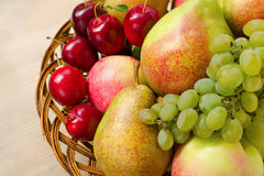 Fruit harvest. Organic fresh apples, pears, grapes and plums in wooden plate Royalty Free Stock Photo