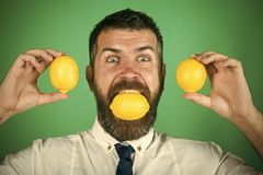 Fruit and healthy organic food. T and healthy organic food. happy man with long beard eat lemon. Dieting and fitness. Vitamin citrus at hipster on green Stock Photography
