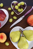 Fruit in heart shape plates on wood table. stock photo