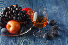 Fruit on her cover look interesting. Cognac served with fruit. stock photos