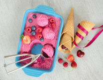 Fruit ice cream with berries and cones. Fruit ice cream with berries, ice cream balls and ice spoon Stock Photography