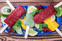 Fruit ice cream on a stick of red currant and blueberries. On a wooden table Stock Photography