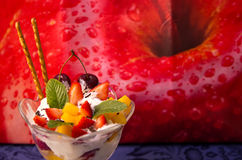 Fruit and ice cream sundae. With cookies and mint leaves in front of a picture of a bright red apple Royalty Free Stock Photos