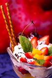 Fruit and ice cream sundae. With cookies and mint leaves on red and blue background Stock Image