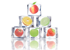 Fruit in ice cubes. Fresh fruit frozen inside ice cubes over a white background Royalty Free Stock Photo