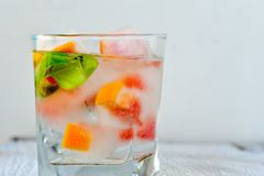 Fruit in ice cubes in water. Grapefruit and mint frozen in ice cubes in water  on black background . Luxurious fresh summer fruit eating. Detox drink Royalty Free Stock Image