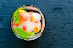 Fruit in ice cubes in water. Grapefruit and mint frozen in ice cubes in water  on black background . Luxurious fresh summer fruit eating. Detox drink Stock Image