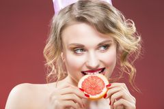 Fruit Ideas. Shy and Caucasian Blond Girl Biting Grapefruit. Slice in Front. Against Red Background.Horizontal Image stock image