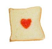 Fruit jam heart shape on slice bread. Fruit jam heart shape on slice bread isolated on white background Stock Photo