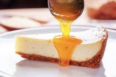 Fruit jam pouring on piece of freshly baked cheesecake. Fresh fruit jam pouring on piece of delicious freshly baked cheesecake on white plate. Topping for sweet Royalty Free Stock Photography