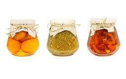 Fruit jams isolated on white background. Orange, mandarin and feijoa jam in glass jars isolated on white background stock photography
