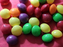 Fruit jelly beans on pink background. So close, colored food royalty free stock photography