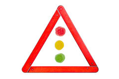 Fruit jelly candies traffic light colors among warning triangle Stock Photos
