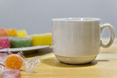 Fruit jelly and a cup of coffee on a gray wooden table. n Royalty Free Stock Photos