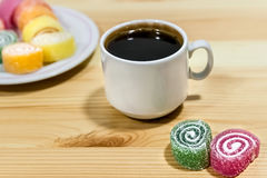 Fruit jelly and a cup of coffee on a gray wooden table. n Royalty Free Stock Image