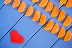 Fruit jelly in the form of mandarin lobules lies on the painted boards next to the heart. The combination of blue, orange and red stock photography