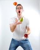 Fruit Juggle. Image of a man juggling 3 pieces of fruit Stock Photo