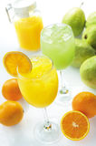 Fruit juice. Two glasses of fruit juice display with a jar of orange juice Stock Photography