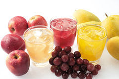 Fruit juice. Three glasses of fruit juice displayed with respective extractive fruits Royalty Free Stock Images