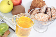 Fruit, juice and cookies. Kiwi, apples, cookies with a peanut, gingerbreads, juice, pistachios on the gray background Stock Photo