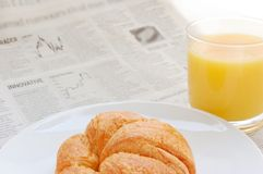 Fruit juice, croissant and business paper. Glass of refreshing orange fruit juice and croissant over business paper with graphs and word 'innovative', macro Royalty Free Stock Photography