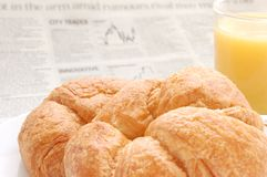 Fruit juice, croissant and business paper. Glass of refreshing orange fruit juice and croissant over business paper with graphs out of focus, macro Royalty Free Stock Photography