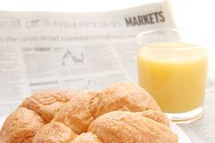Fruit juice, croissant and business paper. Glass of refreshing orange fruit juice and croissant over business paper with graphs and word 'markets', macro Royalty Free Stock Photo