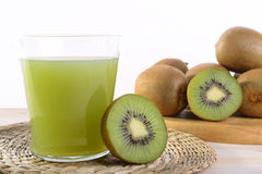 Fruit juice. A glass of kiwi juice with half a kiwi and a wooden tray of kiwis Stock Image