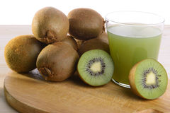 Fruit juice. A glass of kiwi juice with kiwis all around and two halves of the fruit on both sides of the glass Royalty Free Stock Photo